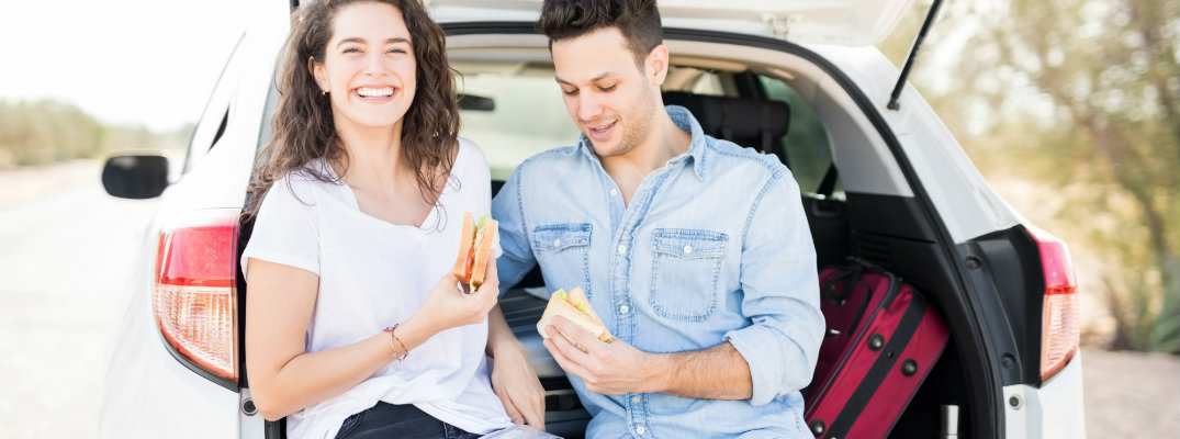 Couple eating snacks out of the boot of their vehicle
