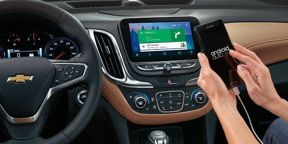 2018 Chevy Equinox interior front hand holding phone paired with infotainment system