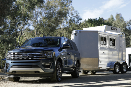 black 2018 ford expedition towing silver camper trailer through forest road