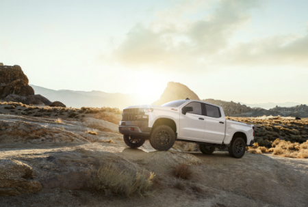 side view of white 2019 chevrolet silverado 1500 scaling desert ridge