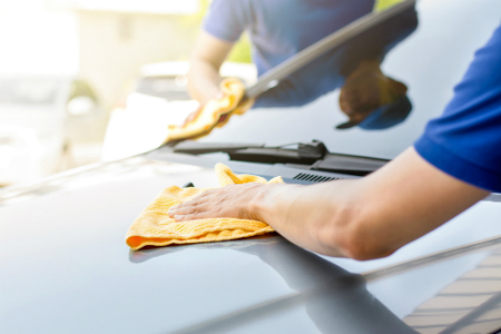 two people cleaning exterior of car with yellow cloths