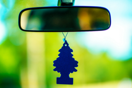 pine tree air freshener hanging from rearview mirror of car