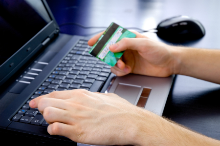 person on laptop with credit card in hand