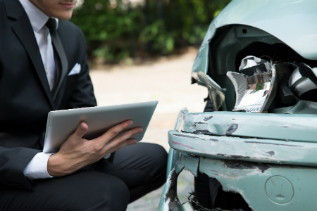 man in suit examining damage on car with tablet in hand