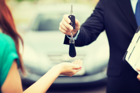 man in suit handing car keys to young woman