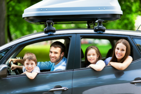 parents and young kids in car with luggage in car together