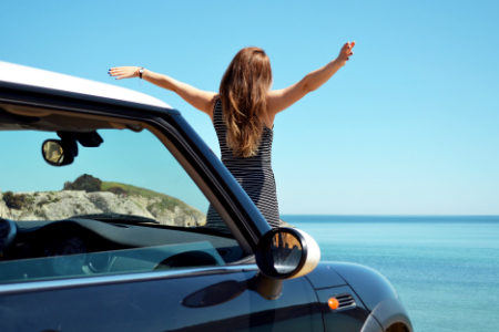 woman standing in front of car with arms stretched outwards towards ocean