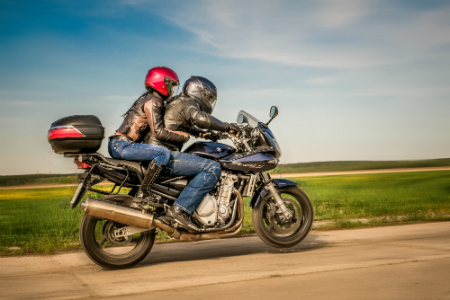 man and woman riding motorcycle together on empty road in flat country