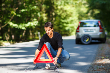 young man placing down triangle reflectors in front of his broken down car on the side of the road