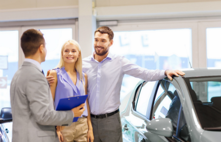 young couple in car dealership next to car talking to car salesman