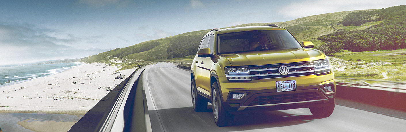 Yellow 2018 VW Atlas Driving on a Coastal Highway