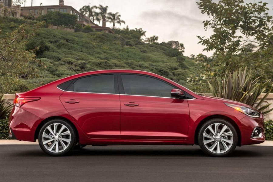 Red 2020 Hyundai Accent from passenger side with trees in background