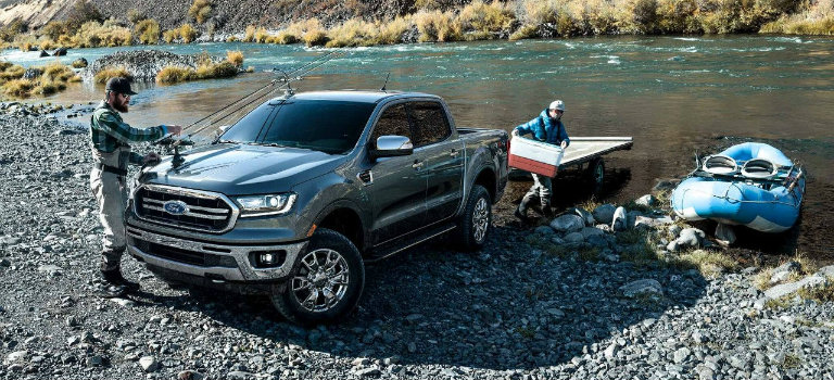 two-men-unloading-fishing-gear-from-silver-2019-Ford-Ranger-next-to-river