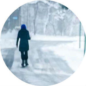 Woman Walking on Snow-Covered Road in Winter