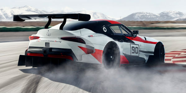 Red, White and Black Toyota GR Supra Concept Rear Exterior Drifting on a Track with Mountains in the Background