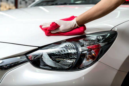 person waxing the hood of a car