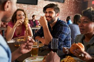 a group of friends in a brick-walled sports bar eating and drinking and laughing