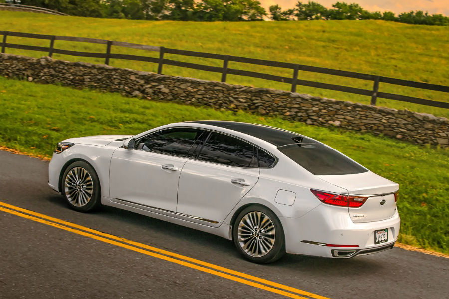 rear shot of the 2018 kia cadenza in white driving on pastoral land