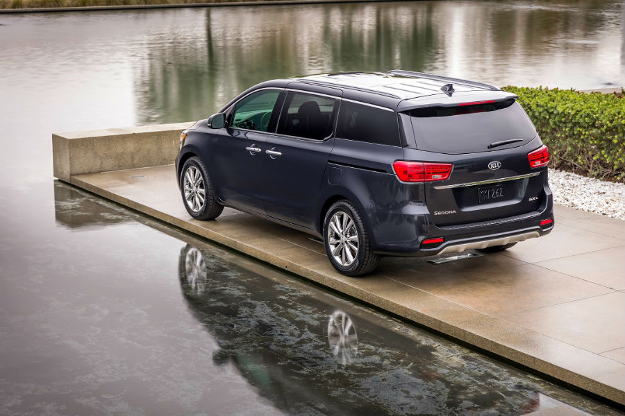 rear of 2019 kia sedona parked on a dock in front of water