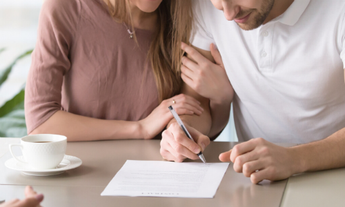 Closeup of two people signing paper