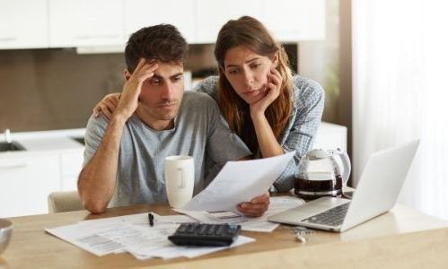 Man and woman holding papers and looking stressed