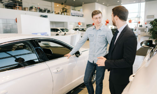 Man and salesman talking by vehicle