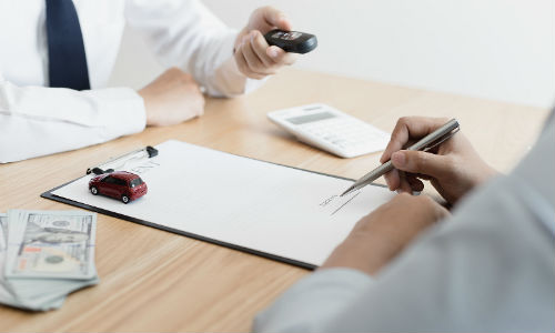 Customer signing car loan payment papers