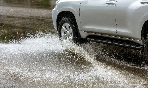 Silver vehicle driving through water