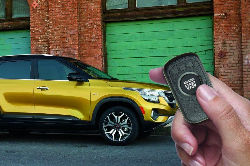 Hand holding remote start fob in front of yellow 2021 Kia Seltos