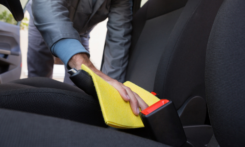 Person cleaning spilled coffee in car with yellow rag