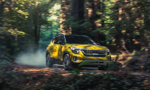 Yellow 2021 Kia Seltos driving in forest