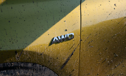 Closeup of mud-covered AWD badge on yellow 2021 Kia Seltos