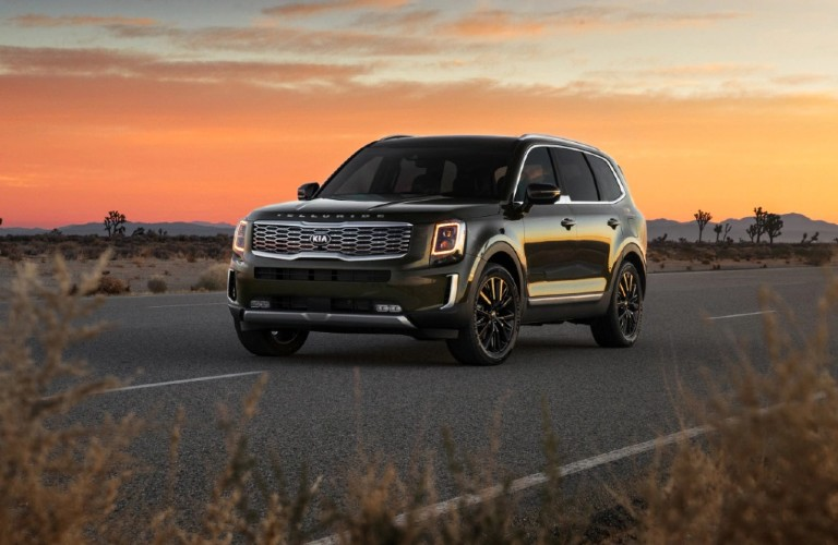 The front and side view of a black 2021 Kia Telluride with a sunset in the background.