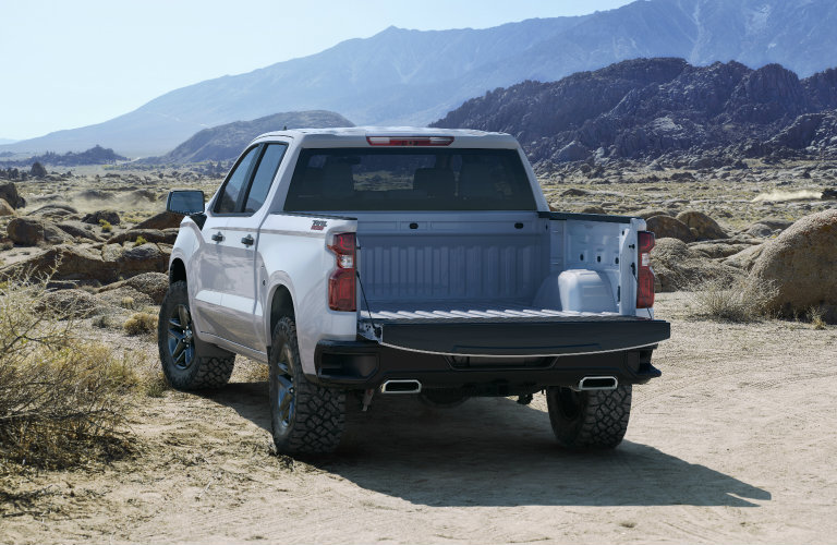 rear view of a white 2019 Chevy Silverado 1500 with mountains in the background