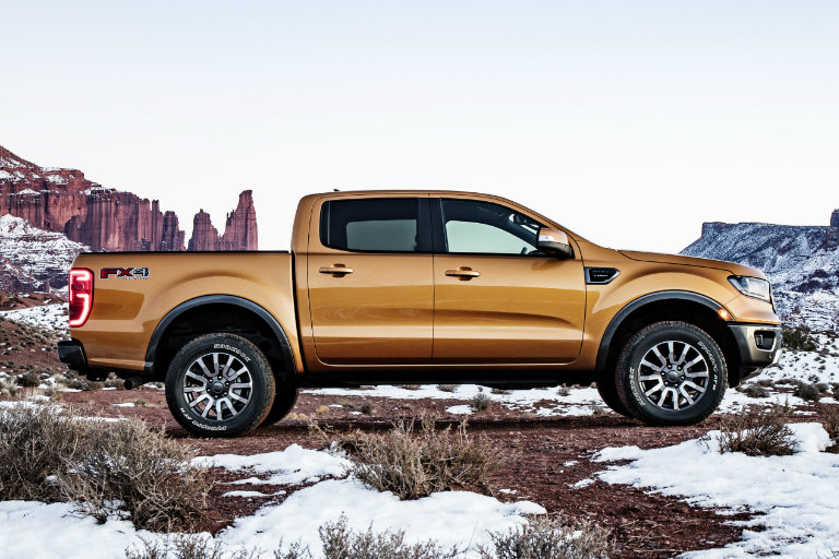 side view of an orange/yellow 2019 Ford Ranger parked in the wilderness