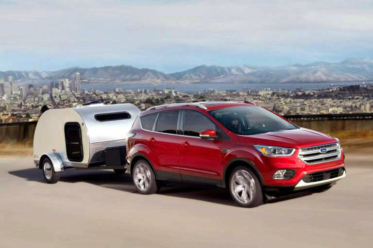 red 2018 Ford Escape towing a small trailer