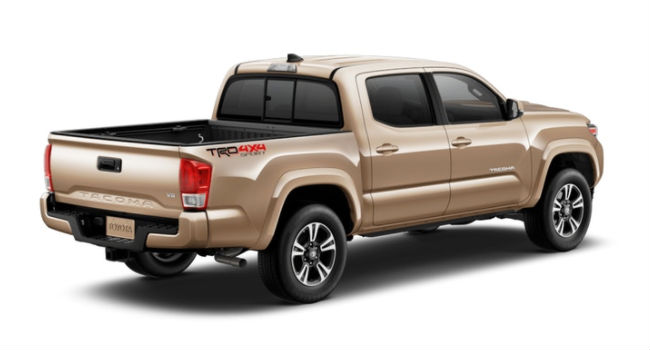 A rear right quarter view of the 2018 Tacoma in a Quicksand paint color