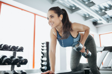 woman exercising with dumbbells at gym