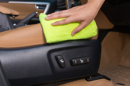 person cleaning interior upholstery of car with neon cloth