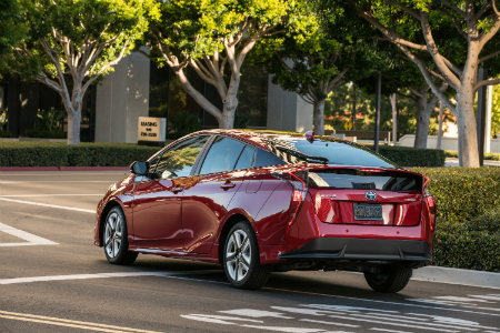 rear bumper view of red 2018 toyota prius driving through intersection