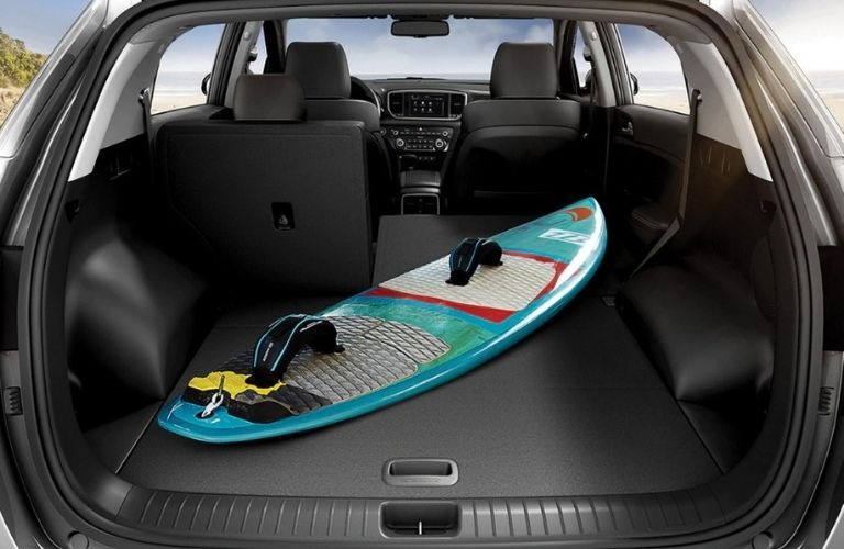 Interior view of the rear cargo area inside a 2021 Kia Sportage with a surfboard inside