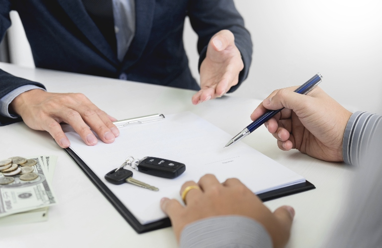 Person signing paperwork for a new vehicle with keys on the table