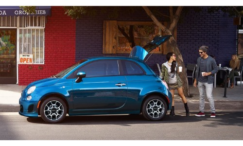 2018 Fiat 500 exterior side shot with blue paint job a as man and woman with coffee load the open trunk