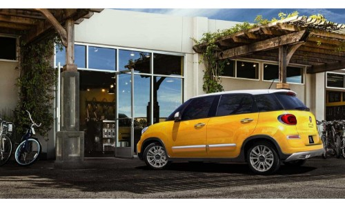 2018 Fiat 500L exterior shot with yellow paint job parked outside a building with bushes and bikes