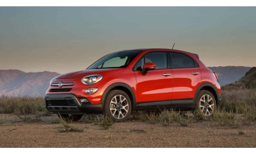 2018 Fiat 500X exterior shot with red paint job parked in an empty plain of wild grass and dirt with a mountain background