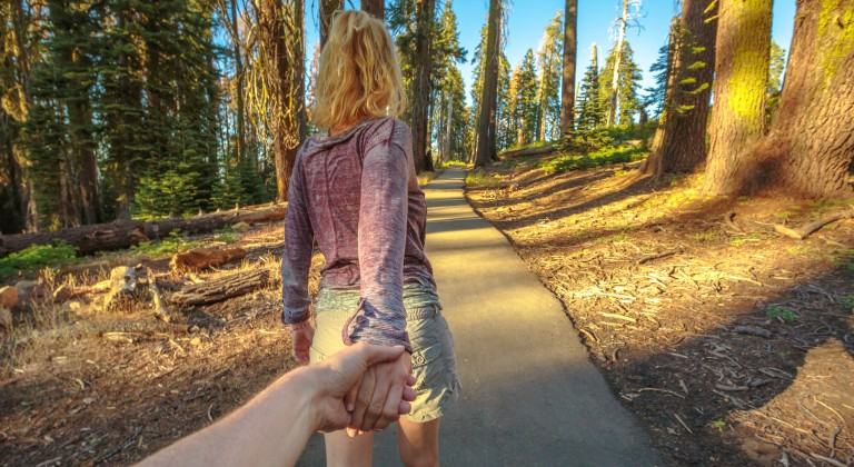 girl pulling somone down a hiking trail with trees
