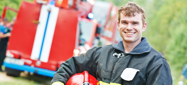 smiling firefighter in front of a fire truck