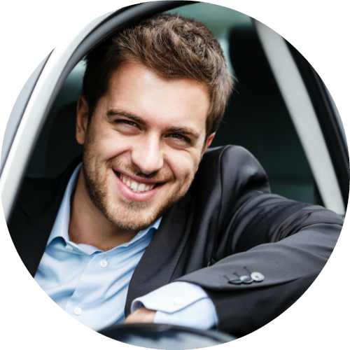 happy man sitting in driver's seat looking out car window