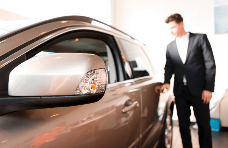 man in suit looking at high-end silver car with closeup of side mirror