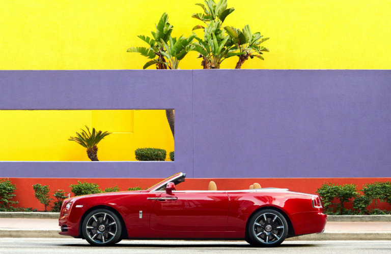 red-Rolls-Royce-Dawn-convertible-parked-in-front-of-purple-and-yellow-wall